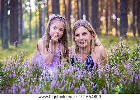 Mother and her daughter in the summer evening in the forest. A happy family in the heather field.