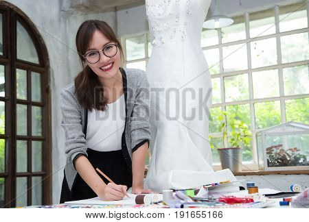 Young female fashion designer are working on drafting a new clothes in studio.