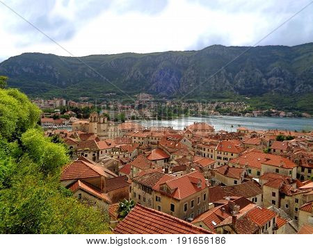 Aerial view of vibrant colored tiled roofs of Kotor Old City on the shore of Kotor Bay, Kotor, Montenegro
