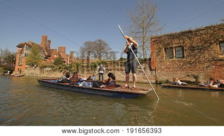 CAMBRIDGE UK-APRIL 10: many tourists enjoy nice weather outside on boat floating on river in Cambridge university the second-oldest university in the english-speaking world in summer on April 10 2017