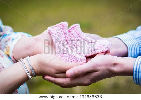 New parents holding baby's socks. Waiting for a newborn.