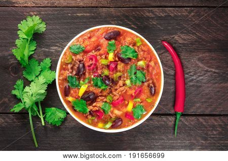 An overhead photo of chili con carne, a traditional Mexican dish with red beans, cilantro leaves, ground meat, and chili peppers, on a dark rustic texture with a place for text