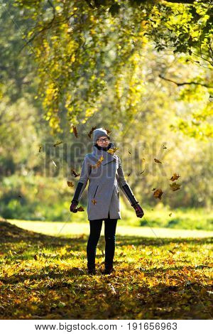 Beautiful autumn portrait of a woman. Autumn leaves, colorful view, beautiful girl. Girl is catching autumn leaves.