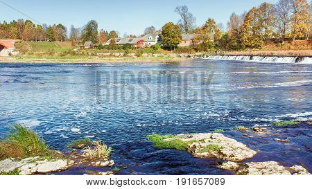 The river in the autumn. Nearby is the widest waterfall in Europe. He is in Latvia, in the city of Kuldiga.