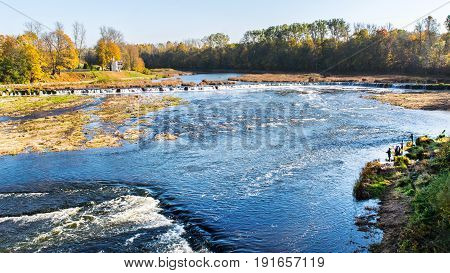 Fishermen on the river with a fishing rods. Next to them is the widest waterfall in Europe. He is in Latvia, in the city of Kuldiga.