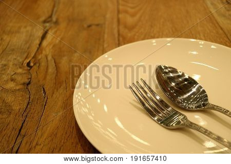 Off White Ceramic Plate with Silver Spoon and Fork on the Wooden Table