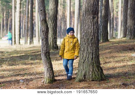 The boy in a yellow jacket strolls through the woods