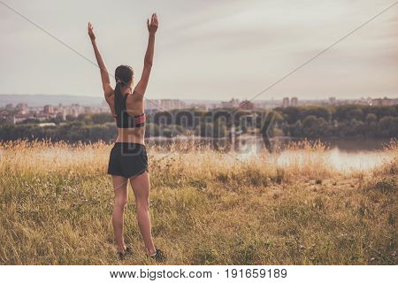 Sporty woman enjoys exercising and looking at city view with her arms outstretched.