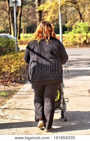 Large-Sized mother walking with baby stroller