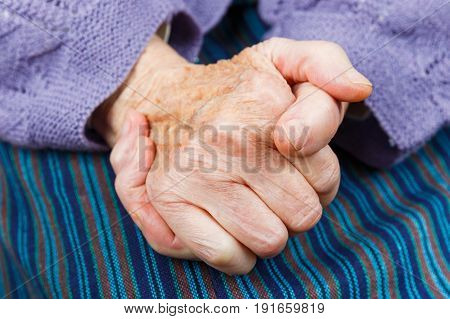 Close up photo of clasped elderly woman hands