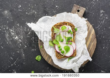 Healthy snack: slice grain bread with ricotta, green peas, radishes, lemon zest and juice. Top view.