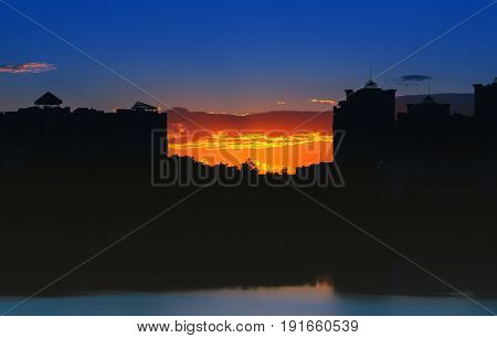 Night city landscape - silhouettes of high-rise buildings against the background of an orange sunset reflected in the lake.