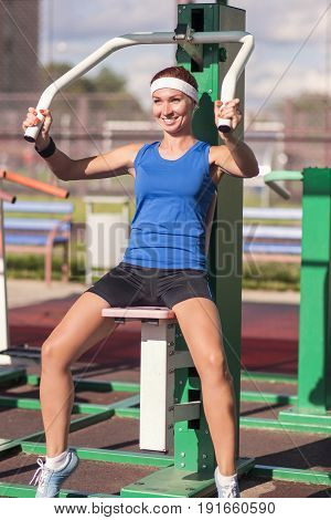 sport Concept and Ideas. Postive Caucasian Female Athlete in Good Fit Having Workout Exercises Outdoor with Weights. Vertical Shot