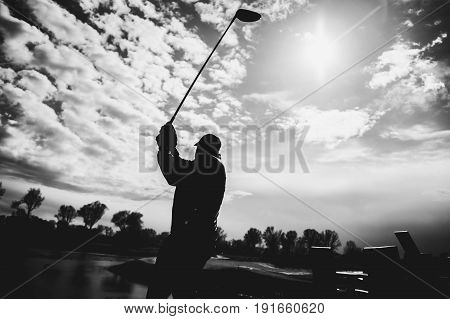 golfplayer hits a ball silhouette with sun and clouds on the background