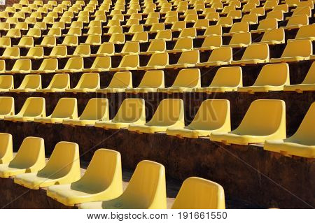 Rows of empty yellow seats in a open-air theatre (amphitheatre)