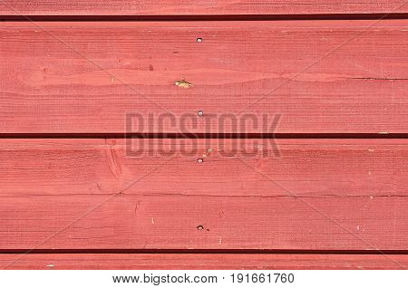 Red pale painted weathered wooden fence with clinched nails