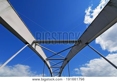 Elements of modern tied arch bridge on picturesque cloudy sky