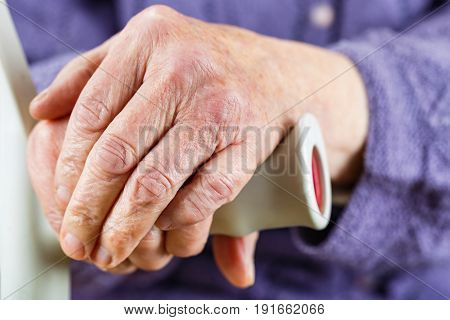 Elderly hands resting on the walking stick