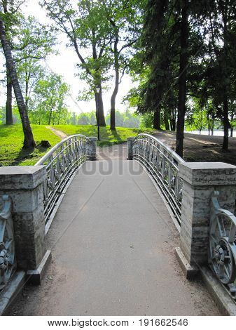 stone bridge across the river on a background of green trees