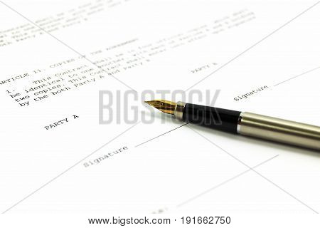 A gold-nibbed pen on a form of a document with a place for a signature