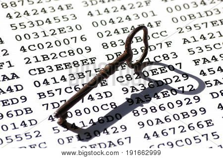 Old-fashioned rusty iron key on a sheet with encrypted data