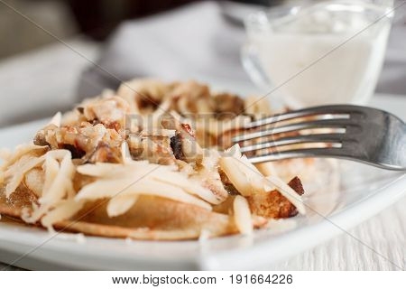 Pancakes with cheese, meat and mushrooms on white plate. Homemade russian traditional dish. Crepes with with filling.