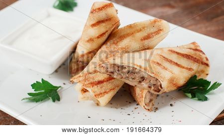 Russian pancakes with meat. Homemade filled by beef crepe rolls on white plate.