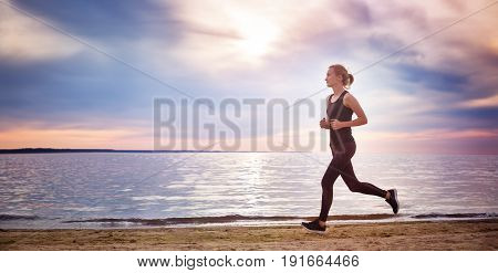 Young woman running on the beach near seaside at sunset. Active person outdoors at the dusk in summer