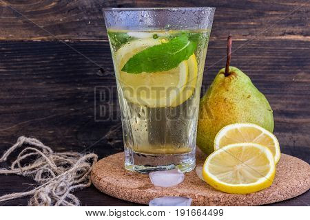 Lemonade Of Ripe Pears With Lemon And Mint On A Dark Background. Concept Of Healthy Eating.