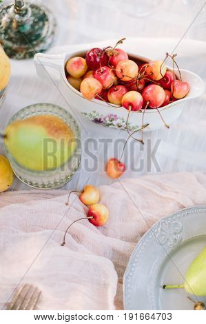 picnic, vegan food, holiday concept - ripe delicious red and yellow cherries with stems, pears on decorated table for the party, fruit plates and dishes, white tablecloth, clean and fresh, flat lay