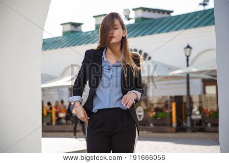 Beautiful woman with long healthy hair. Fashionable women's look with black jacket and blue blouse. Fashion concept