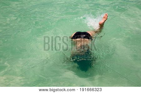Top view of a girl diving into clear sea water