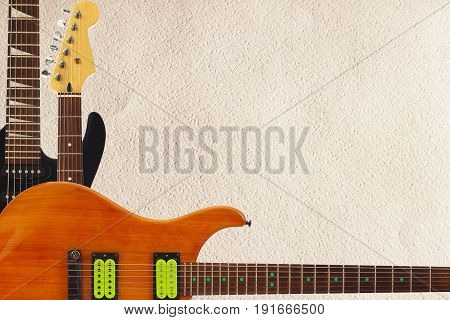 Mahogany and black electric rock guitars and headstock on the rough cardboard background with plenty of copy space.
