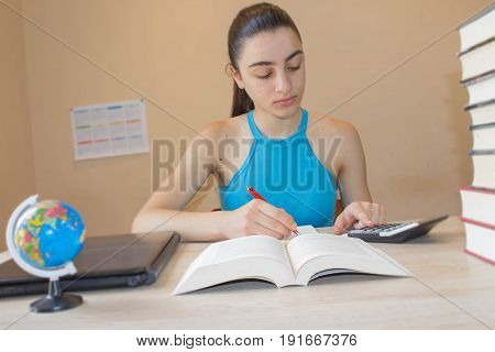 Open book hardback colorful books on wooden table. Young girl sitting at desk at home doing homework
