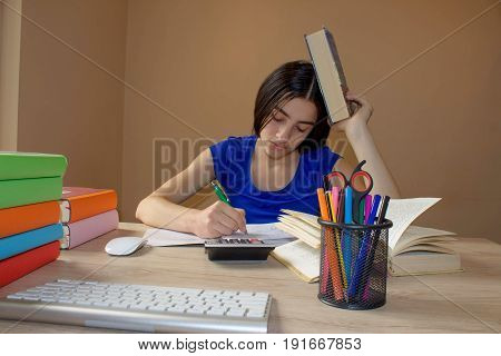 Girl studying. Thoughtful young Girl sitting at desk with books. Thoughts education creativity concept