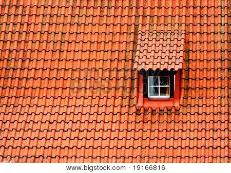 Red tile roof with a window. Prague, Czech Republic.