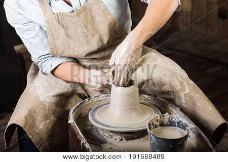 pottery, workshop tools, ceramics art concept - man hands work with potter's wheel, the fingers form the shape of raw fire clay, young male sculpt a utensils with a sponge, master in apron, top view