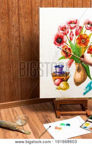 Professional painter drawing watercolor flowers. Unrecognizable artist's hand paints bouquet picture . Drawing lessons, art school, young artist concept