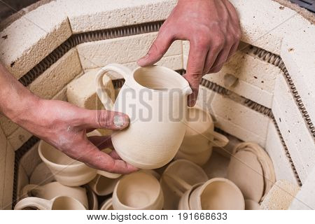 pottery, workshop, ceramics art concept - top view of electric oven for roasting of unbaked clay products, male hands putting the jug in the kiln, some unfinished cups and utensils