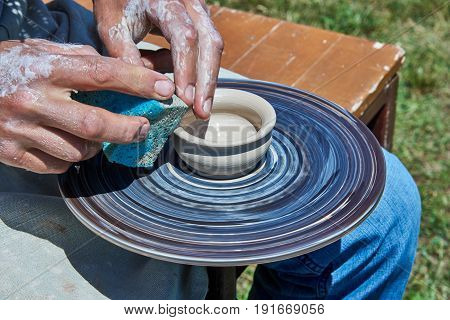On the potter's wheel there is a clay cup. Potter level the surface of the cup with a sponge