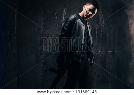 Tattooed killer with sniper rifle in black cloth, studio shoot. Armed white gangster man with weapon and tattoo on dark background with free space. Outlaw, ghetto, murderer, robbery concept