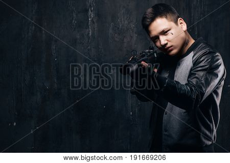 Sniper with tear tattoo on face and rifle close-up. Armed asian killer man with weapon and tattoo on dark background with free space. Outlaw, ghetto, murderer, contract murder, robbery concept