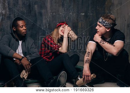 Group of alcoholic young people communicates at students party. Youth addiction problem. Laughing drunk caucasian girl holding alcohol bottle, two guys with tattoo sits near .