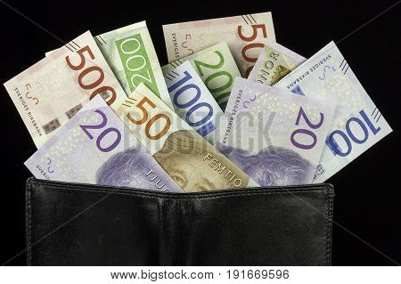 Wallet with Swedish Krona Currency on black background.