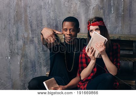 Interracial classmates couple taking selfie on phone. Black guy and white girl are studying together. Students have fun