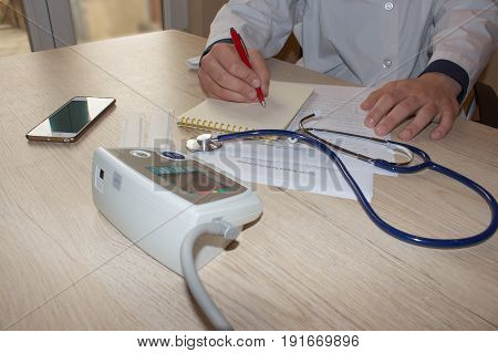 Doctor appoint prescription drugs to patients. Doctor working at table in office