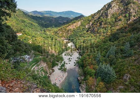 Tourists enjoy on the banks of the River Ardeche near the village of Thueyts in the Ardeche department in France