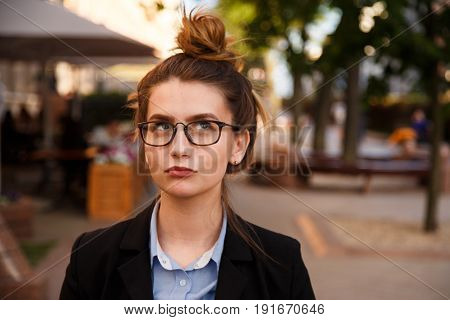 Portrait of young woman in glasses is pondering outdoor
