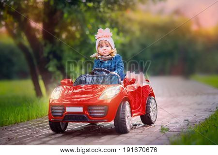 Fashioned Little girl with toy red car cabriolet