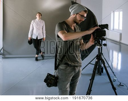 Professional photographer setting the camera while studio shooting session. Backstage of photoshoot